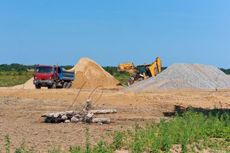 Bryta sten den sandatt bryta, lastbilen och grävskopan bredvid en hög av sand arkivbilder
