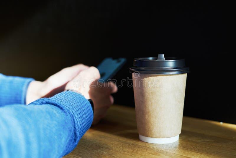 Bryter äter lunch brunt pappers- exponeringsglas för det disponibla hantverket med kaffe, affärsmannen som använder smartphonen,  royaltyfria bilder