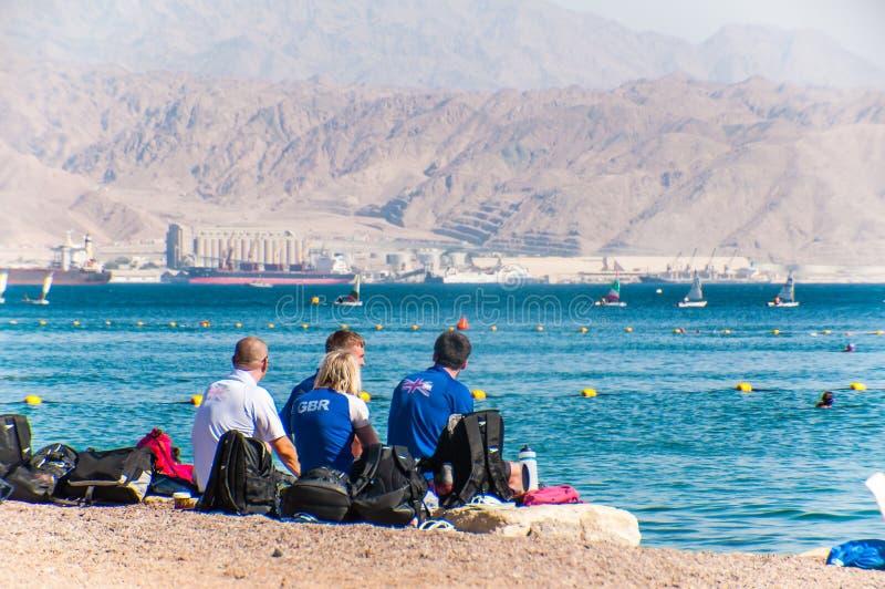 Brytyjscy dopłynięcie drużyny sportowowie siedzi na plaży podczas stażowego dnia w Czerwonych wodach morskich w Eilat, Izrael fotografia stock