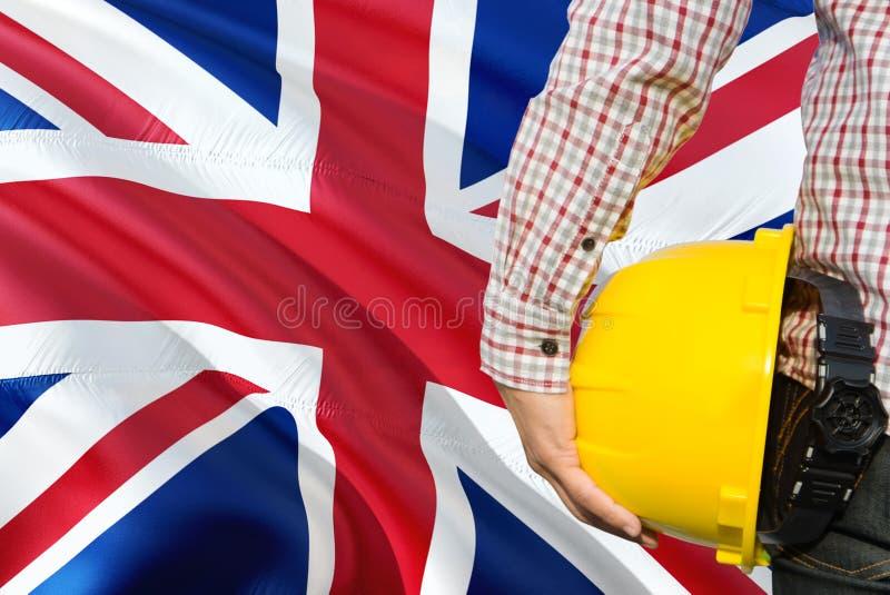 Brytyjski inżynier trzyma żółtego zbawczego hełm z machać Zjednoczone Królestwo chorągwianego tło Budowy i budynku poj?cie fotografia stock