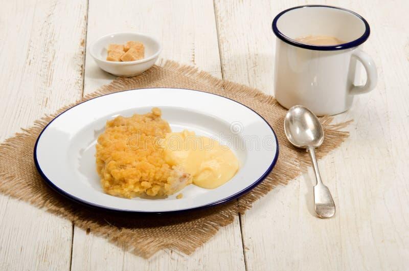 Brytyjski jabłko rozdrobni z custard na emalia talerzu fotografia stock