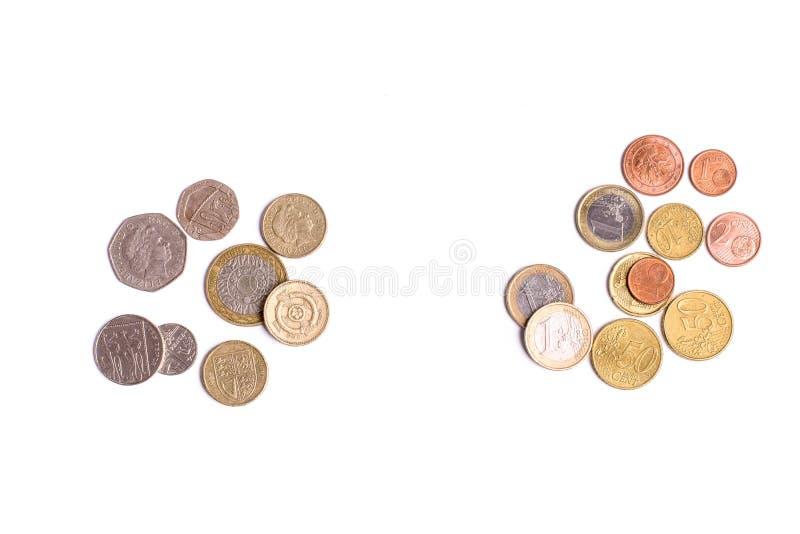 Brytyjskie Funtowe monety i euro monety na białym tle fotografia royalty free