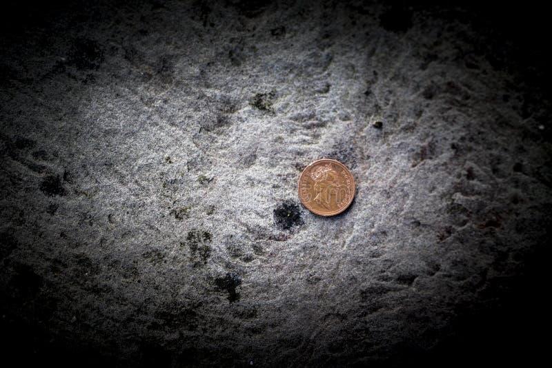 Brytyjskiego szterlinga jeden cent na betonu podłogowym dowiezieniu lub pens zdjęcie stock