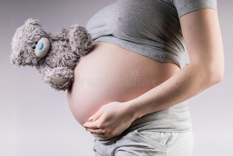 Brzemienność Kobieta w ciąży mienia brzuch na małym zabawkarskim misiu pluszowym obrazy stock