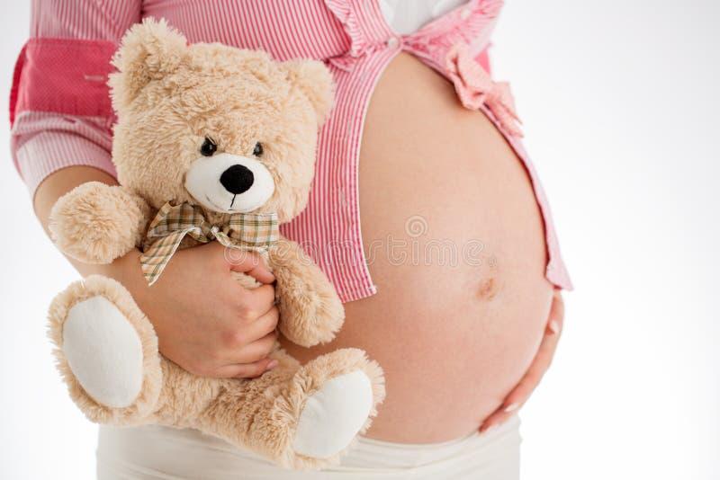 Brzemienność Kobieta w ciąży mienia misia zabawka w jego ręce, st obrazy royalty free