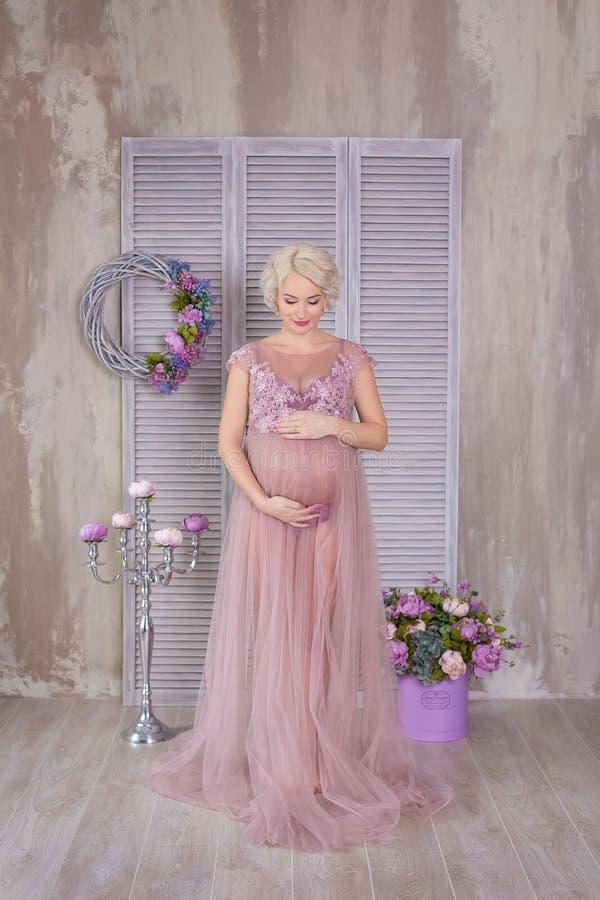 Brzemienność, macierzyństwo i szczęśliwy przyszłości matki pojęcie, - kobieta w ciąży w powiewnej fiołek sukni z bukietem kwitnie zdjęcie royalty free