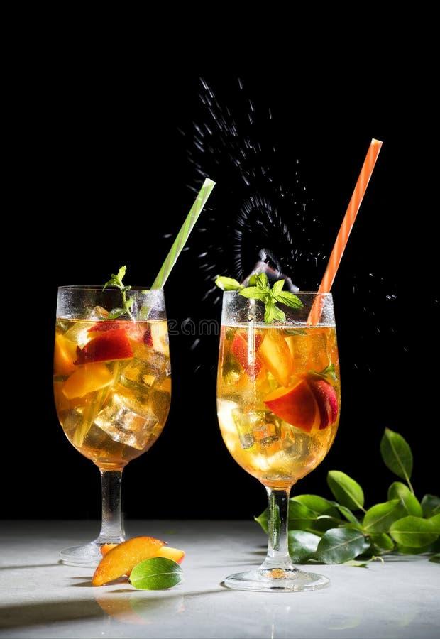 Brzoskwini lata lodowy koktajl lub herbata, sangria z brzoskwinią z pięknym pluśnięciem, kopii przestrzeń, czarny tło zdjęcia stock