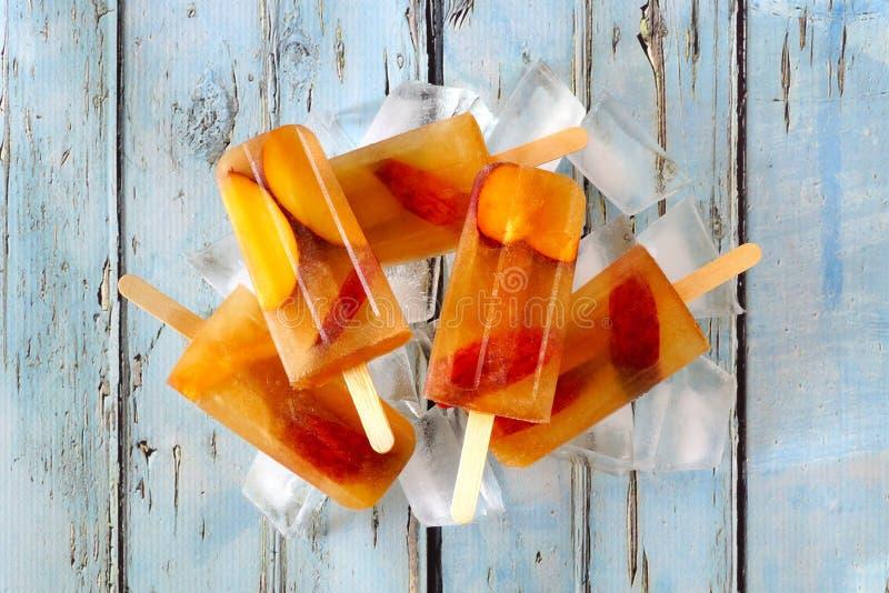 Brzoskwinia zamrażał herbacianych popsicles z lodem na nieociosanym błękitnym drewnie obrazy stock