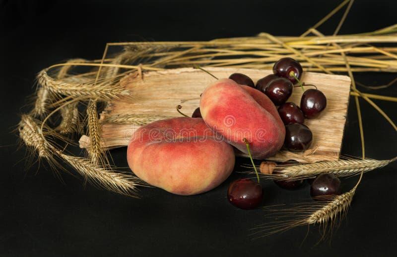 Brzoskwinie, wiśnie, pszeniczni ucho fotografia stock