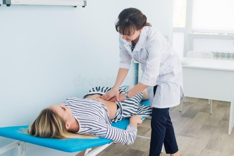 Brzuszny egzamin, lekarka egzamininuje podbrzusze pacjent zdjęcie stock