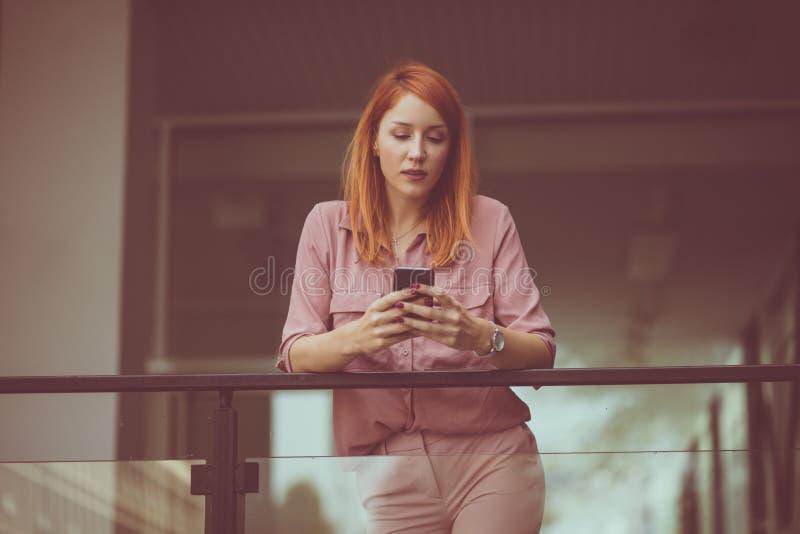 Bsinesswoman unter Verwendung des Handys auf der Straße Stadt L lizenzfreie stockfotografie