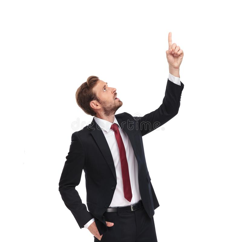 Bsuinessman in awe points up and looks up to side royalty free stock images
