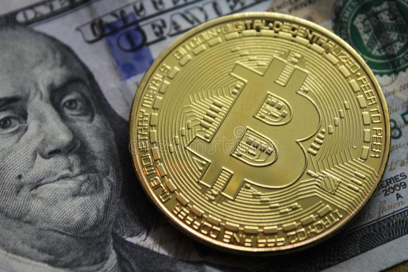 BTC Coin and banknotes.Bitcoin crypto-currency on dollar notes. Bitcoin Coin on a Dollars. Golden metal bitcoin on dollar bills background. Exchange bitcoin for royalty free stock image