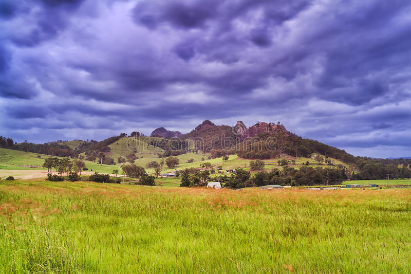 BTops gloucester Rd farm mount. Remote agricultural farm in the middle of green pasture filed under Gloucester tops rocky mountains at sunset in Australia royalty free stock photo