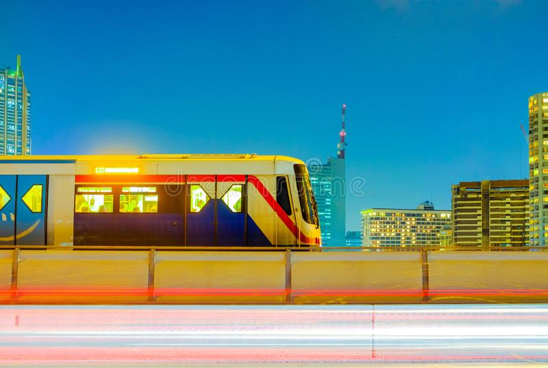 BTS Sky Train on cityscape background and light trails of traffic moving on evening time. And after work, BTS Sky Train is a mass transit system in Bangkok to stock image
