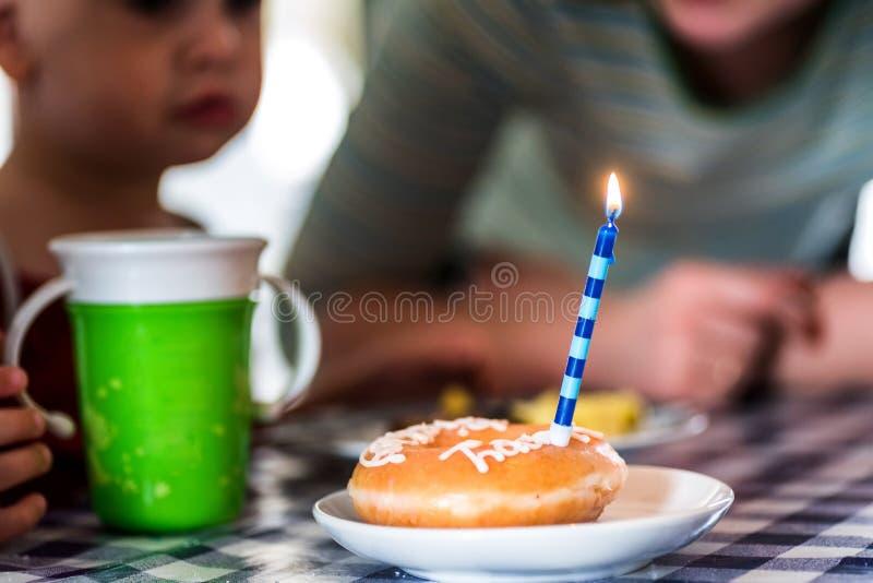 Buñuelo del feliz cumpleaños con la vela en la placa de postre blanca en la tabla delante del bebé imagenes de archivo