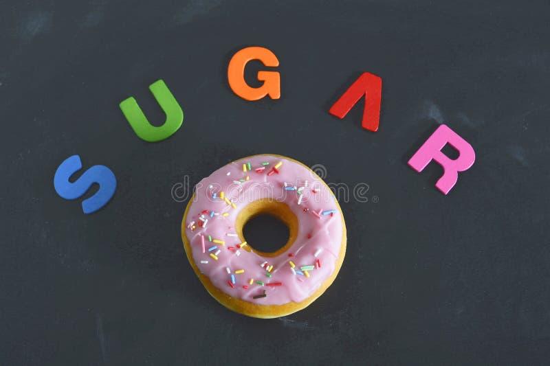 Buñuelo delicioso de la tentación con concepto malsano del apego del azúcar de la nutrición de los desmoches fotos de archivo
