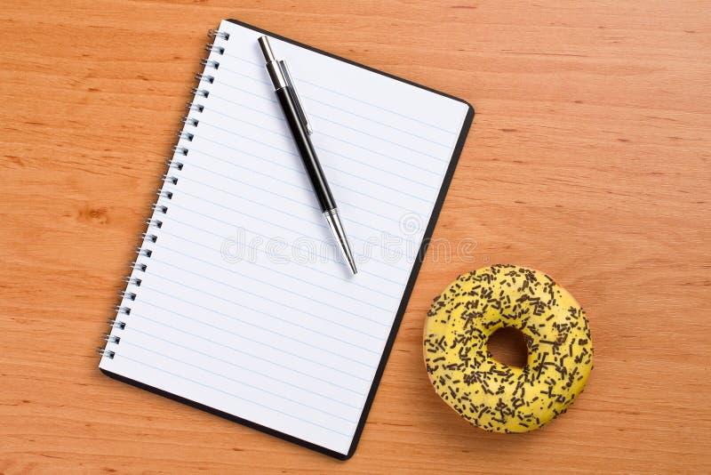 Buñuelo dulce y cuaderno espiral foto de archivo