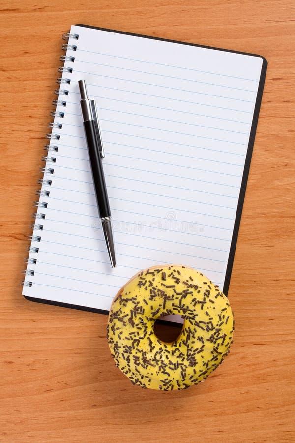 Buñuelo dulce y cuaderno espiral fotos de archivo libres de regalías
