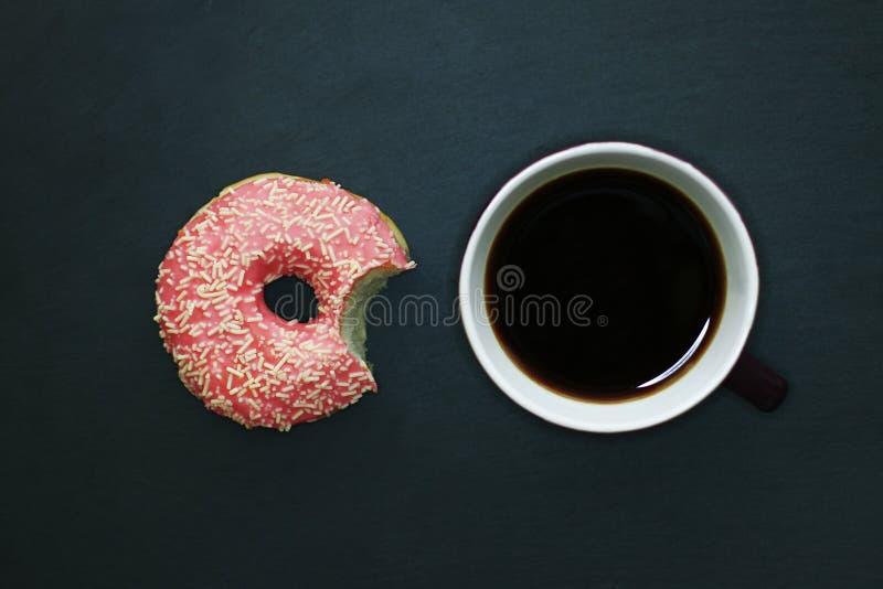 Buñuelo mordido en esmalte rosado y taza de café en el fondo oscuro, visión desde arriba fotos de archivo libres de regalías