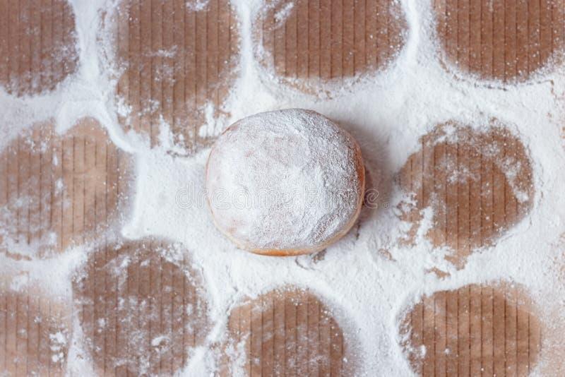 Buñuelo pasado dejado en la caja, rodeada con las impresiones en azúcar en polvo foto de archivo