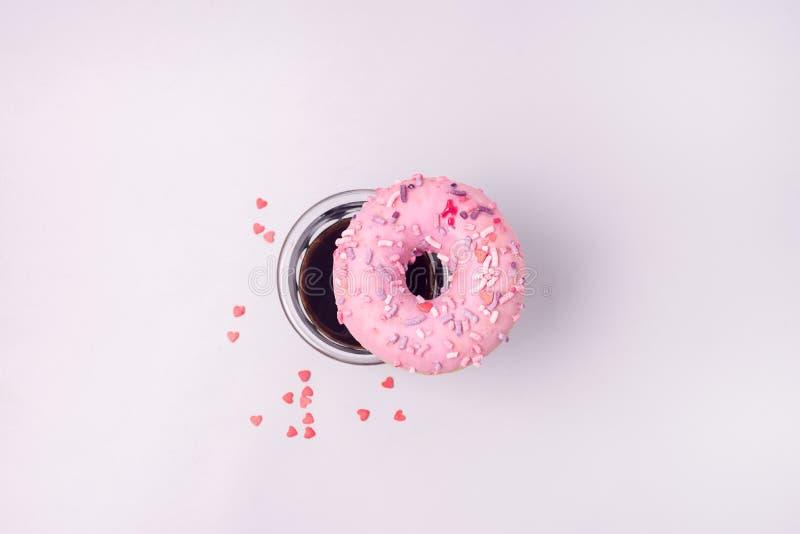 Buñuelo rosado de Fesh con el buñuelo plano y el café de la opinión superior de la endecha de Americano del café foto de archivo