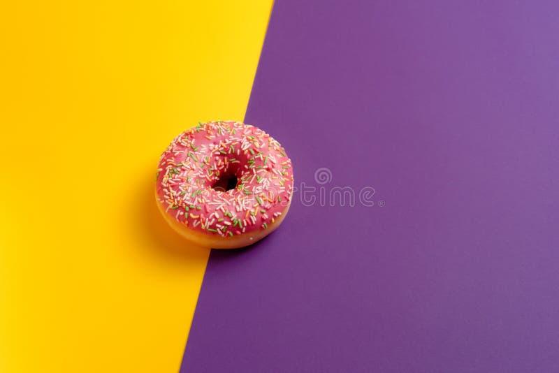 Buñuelo rosado en espacio de color morado oscuro amarillo y violeta de la copia de la opinión de top del fondo foto de archivo
