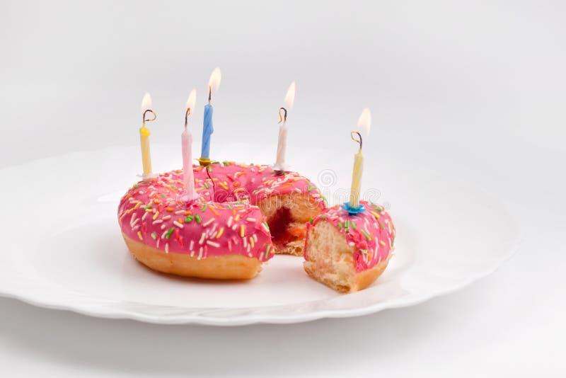 Buñuelo rosado en la placa blanca como la torta de cumpleaños con las velas en el fondo blanco imagenes de archivo