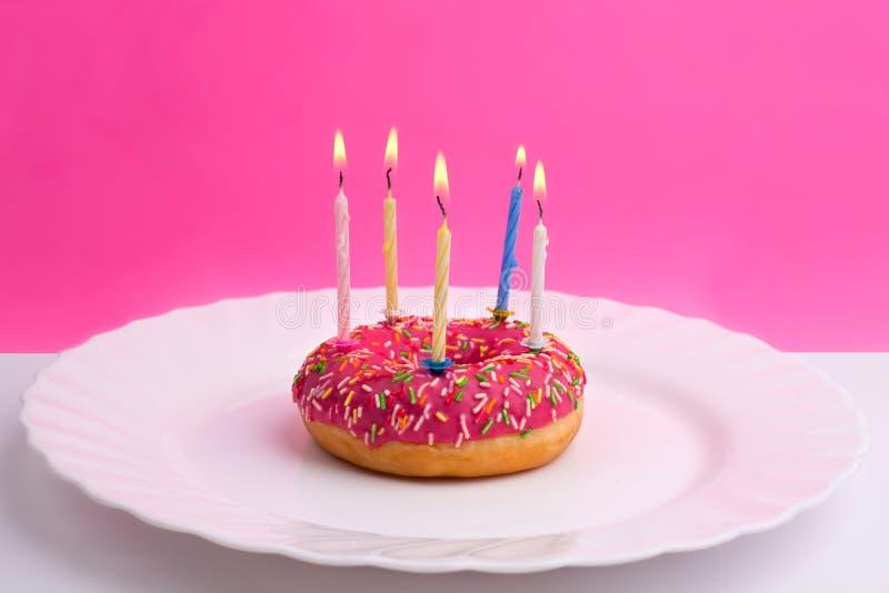 Buñuelo rosado en la placa blanca como la torta de cumpleaños con las velas en el fondo blanco y rosado fotos de archivo libres de regalías