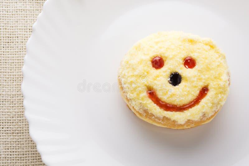 Buñuelo sonriente en una placa blanca imagen de archivo libre de regalías