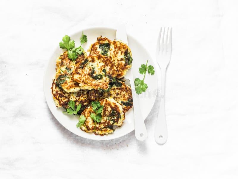 Buñuelos de los calabacines de la espinaca - bocados vegetarianos deliciosos, aperitivos, desayuno en un fondo ligero imagenes de archivo