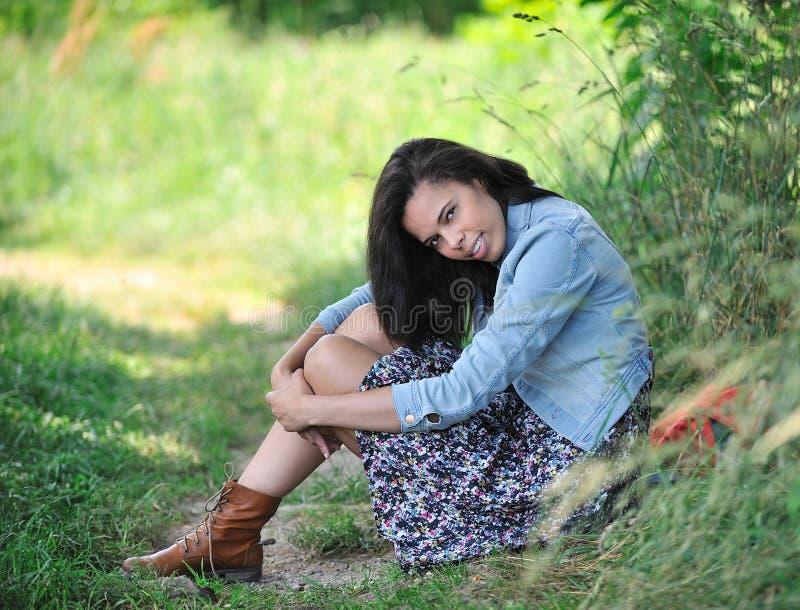 Bu di seduta Biracial della giovane donna una strada rurale immagine stock libera da diritti