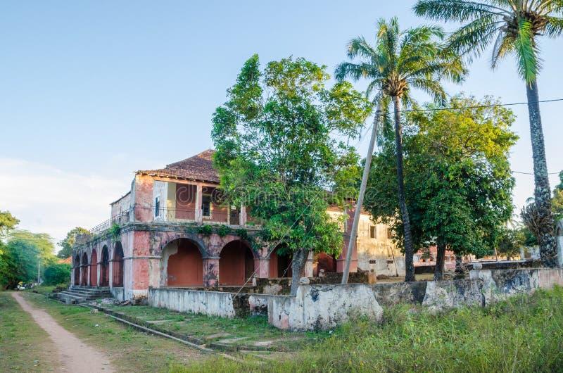Bubaque, Guinea-Bissau - 11 dicembre 2013: Manson rovinato e vegetazione tropicale accanto al percorso della sporcizia fotografia stock libera da diritti
