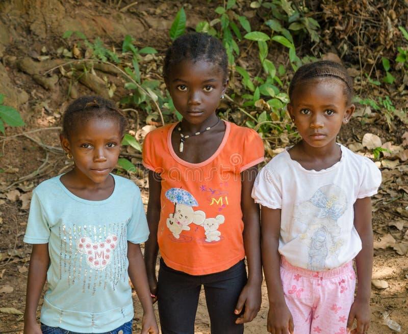 Bubaque, Guinea-Bissau - 9 dicembre 2013: Ritratto ragazze africane non identificate di tthree di giovani sul percorso della spor immagine stock