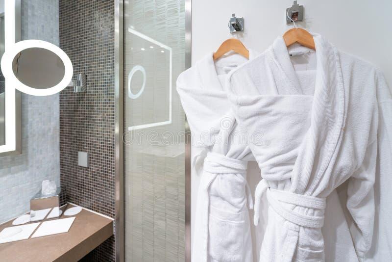 Bubbelbadtid: Rena vita badrockar på hängare i ett badrum Hur man håller din badrock ren och fluffig - Alltid fläckprov arkivbild