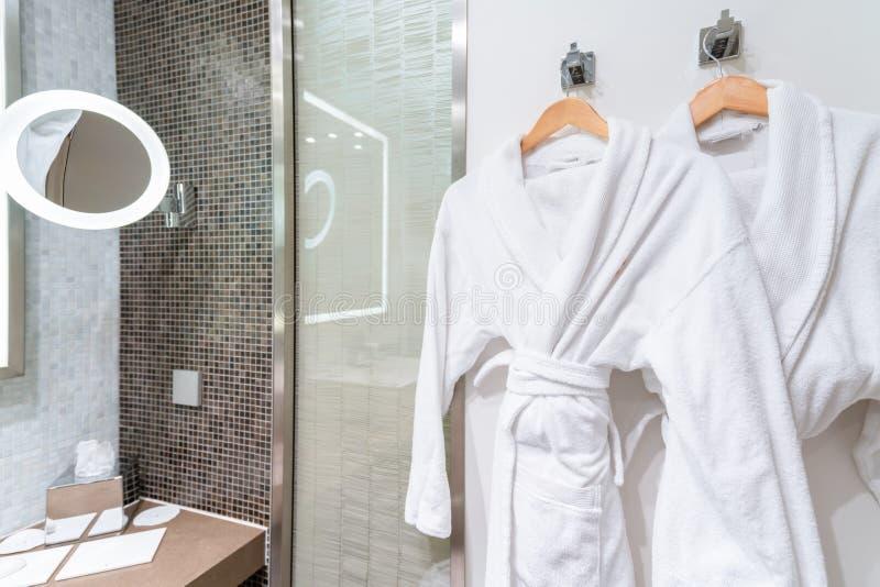 Bubbelbadtid: Rena vita badrockar på hängare i ett badrum Hur man håller din badrock ren och fluffig - Alltid fläckprov royaltyfri fotografi
