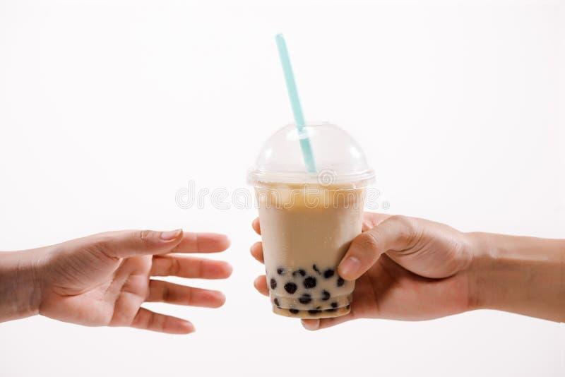 Bubblan mjölkar te - räcka att rymma A plast- exponeringsglas av Taiwan med is mi arkivfoton