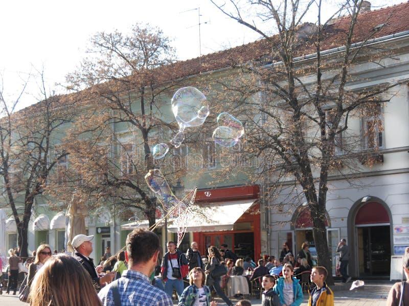 Bubble maker entertaining kids on the street. Man making big bubbles on the street, to entertain kids royalty free stock photo