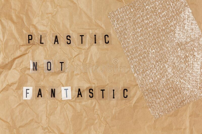 Bubble wrap, phrase from letters on transparent base Plastic not fantastic on brown crumpled craft paper. Eco, zero waste concept. Flat lay, top view royalty free stock photos