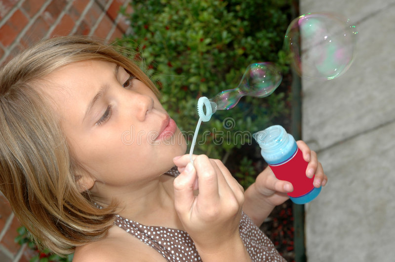 Bubbles in Action. Side view of a eight year old girl blowing bubbles. Child in the action of blowing bubbles royalty free stock images
