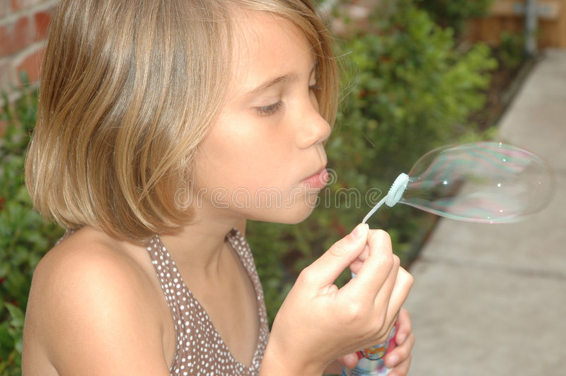Bubbles in Action. Side view of a eight year old girl blowing bubbles. Child in the action of blowing bubbles royalty free stock photography