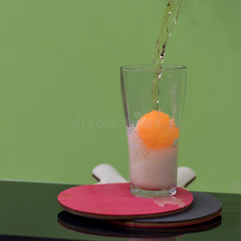 Bubbles of beer in a glass with a ping pong ball. Close-up shots of beer bubbles in glass and orange ping pong balls, which have green walls as backgrounds royalty free stock image