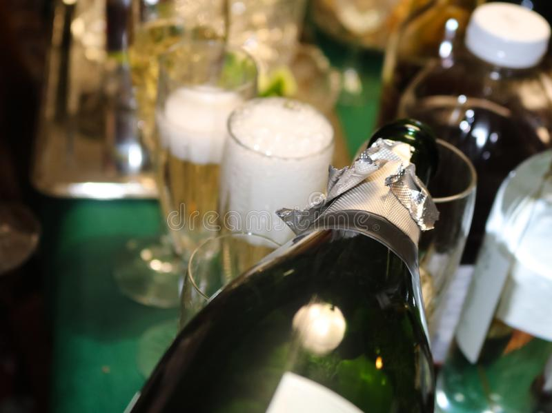 Bubbles coming off poured champagne in a foamy glass with surrounding bottle shapes and more champagne being poured. Selective focus royalty free stock photography