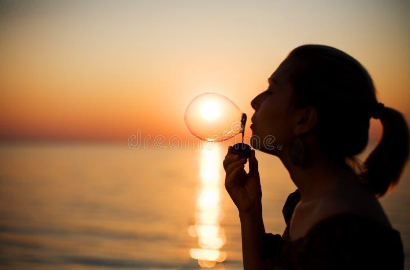 bubbles flickan som gör över tvålsolnedgång royaltyfri foto