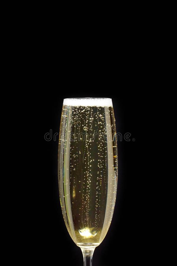Bubbles in a glass of Champagne on a black background. A Close-up of a champagne flute with bubbles and foam on a black background stock image