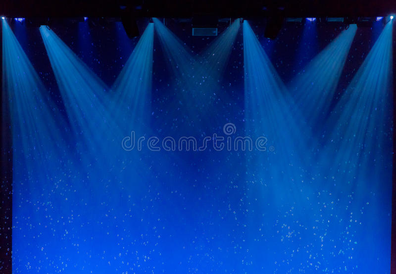 Bubbles and rays of blue light through the smoke on stage stock image