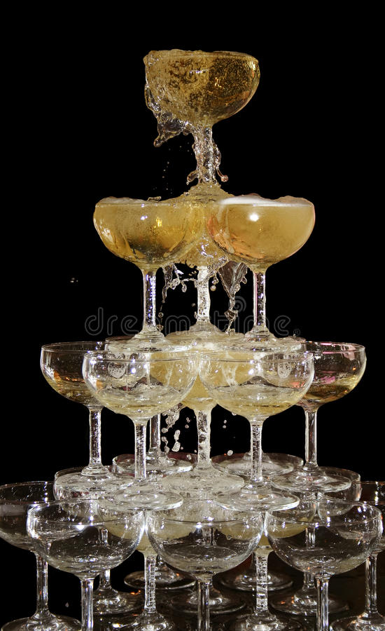Bubbles of Wine spill over. In Wedding Wine Glass. background is black isolate royalty free stock image