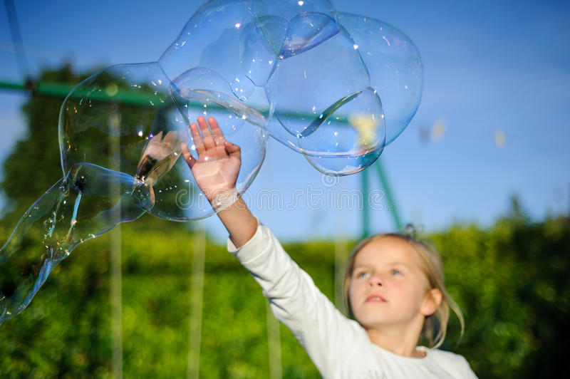 Bubbles. A young girl playing with bubbles royalty free stock photo