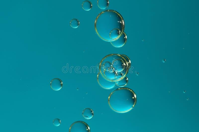 Bubblor för flödande vatten över en massiv blå bakgrund royaltyfria foton