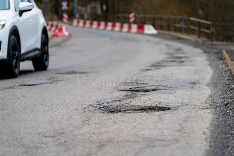 Buca - degradazione dell'infrastruttura Stato sfavorevole del fondo stradale Stagione di inverno Foro nell'asfalto, strada perico fotografia stock